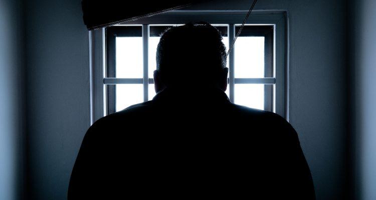 Foto de um homem na sombra, representando alguém que poderia estar cometendo fraude no reembolso corporativo