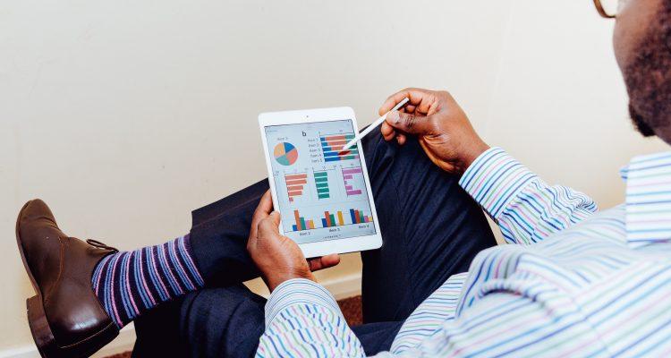 Foto de homem com tablet na mão avaliando gráficos que mostram que a empresa conseguiu aumentar a produtividade - Photo by Adeolu Eletu on Unsplash